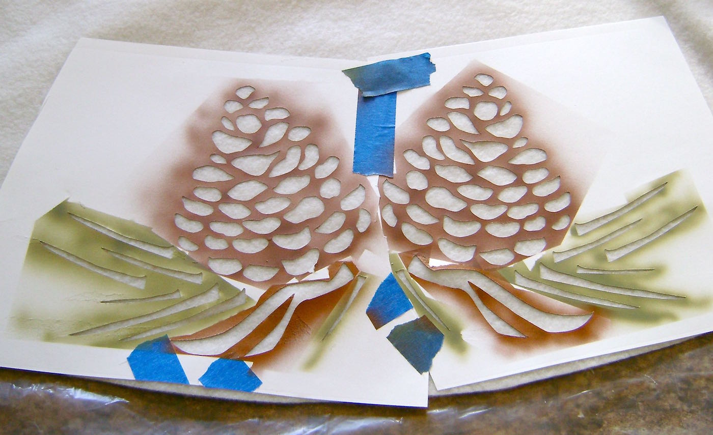 step 9 - Overlap the two stencils to form one large stencil, tilting the images slightly to match the pine cone positions in the skirt photo. Cut around open areas that are blocked by the overlap. Center the stencil on one of the skirt pieces with the bottom edges of the image one-inch from the bottom of the skirt.