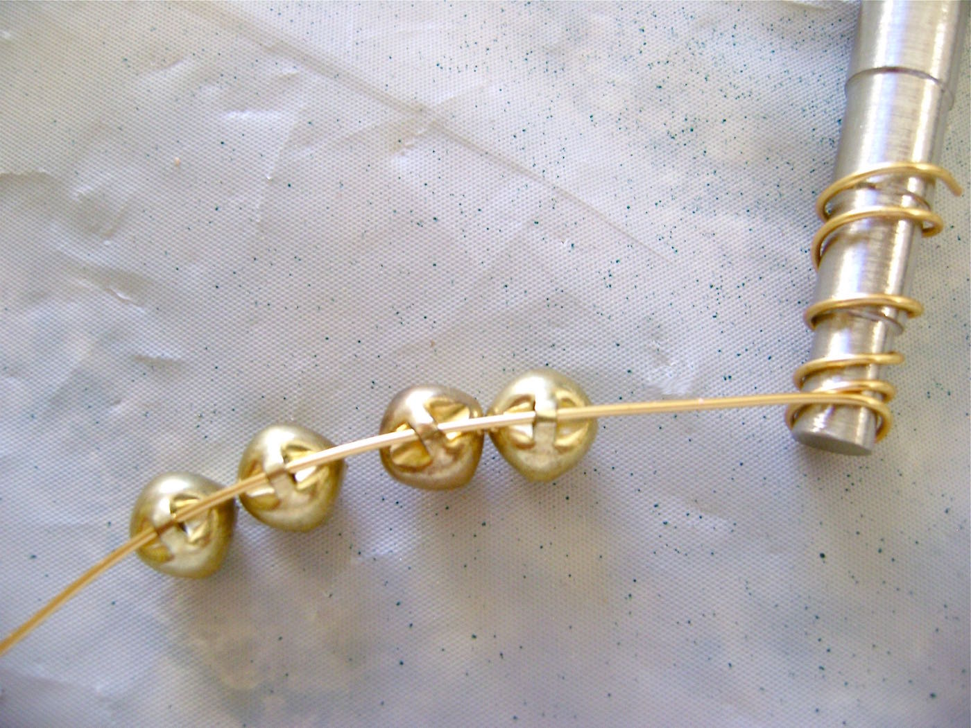 step 12 - To create the decorative bell feature at the top, wrap gold wire around a small round object like a pen or screw driver, 4 or 5 times. Slip the wire off. Leave a tail of about three inches and add the tiny bells.
