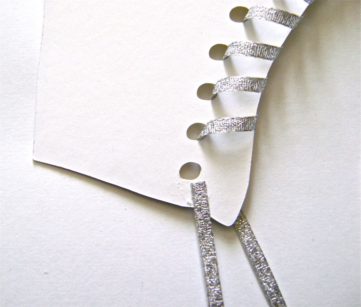 """step 5 - When the ribbon is secured to the wrong side, flip the skate over and thread the ribbon through all the holes in the skate except the first one at the top. Turn the skate over and glue the 11"""" piece of ribbon to the card stock above the first hole. Set aside."""