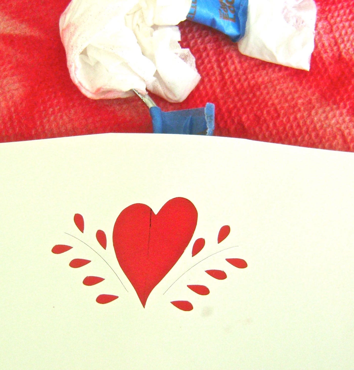step 5 - Stick the heart stencil on the center of the hanger.  Airbrush it with white paint.