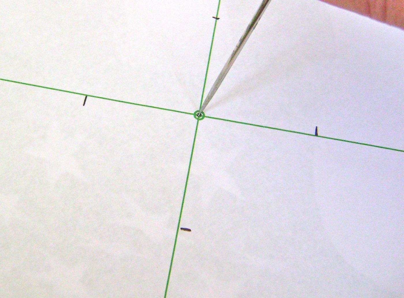 step 4 - Place the template over the printed page.  Use a thick needle to poke a whole through the paper center and through the printed square.  Use the needle to also poke holes in the four corner circles on the template.  Cut on the four diagonal green lines from the outer edge to the black horizontal lines.  Set aside.