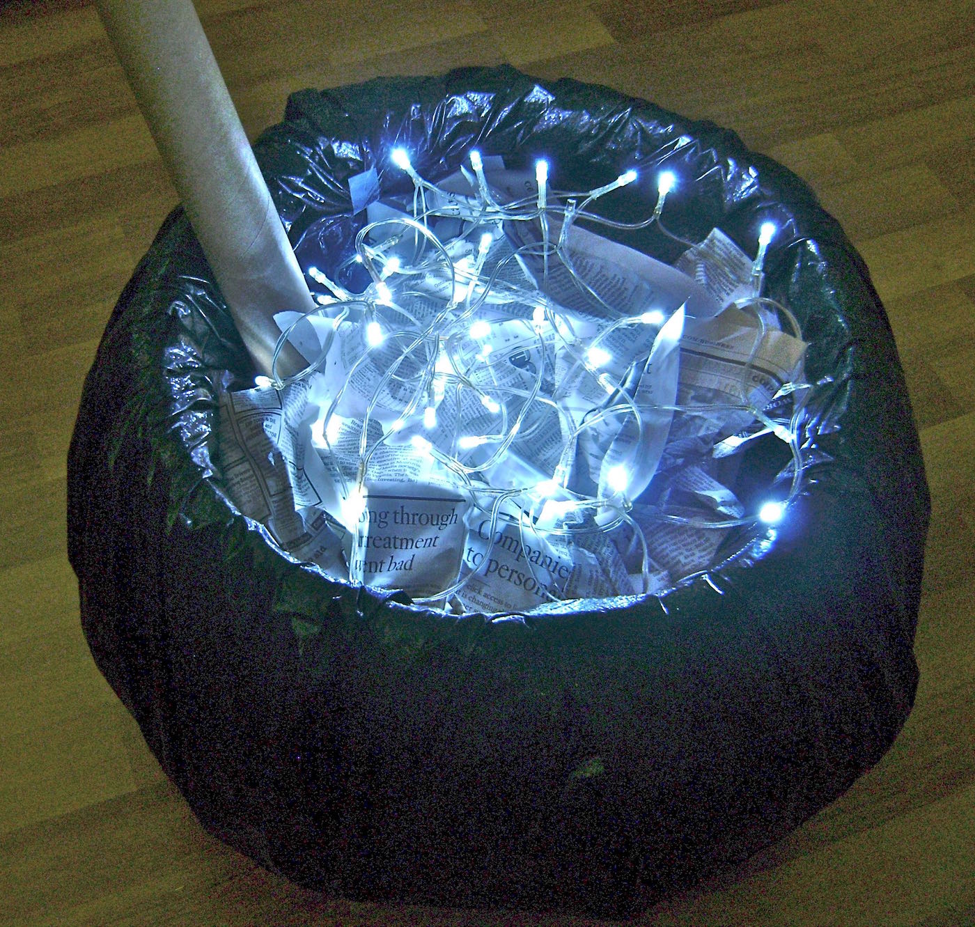 step 14 - Fill the cauldron with crumpled newspaper almost to the top of the container.  Scatter the lights about.