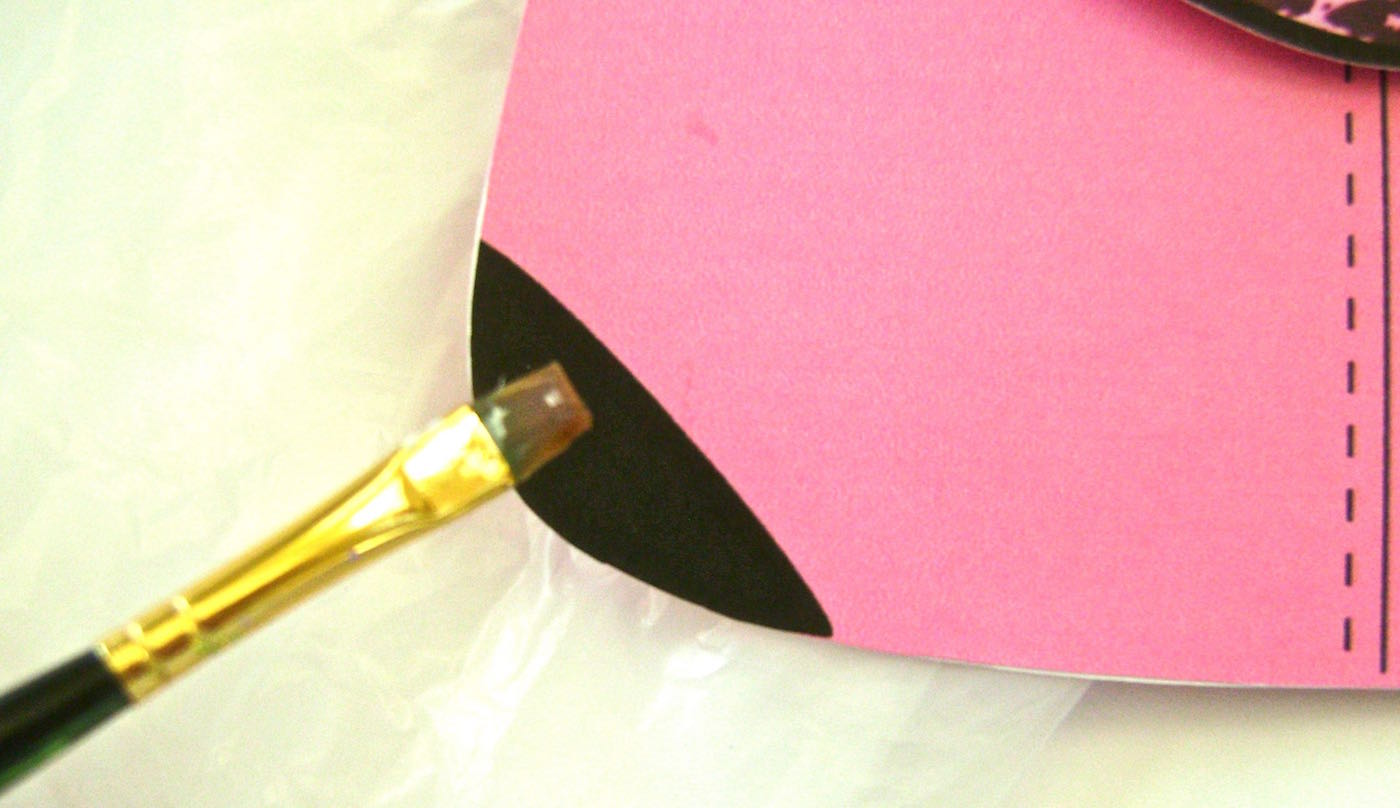 step 8 - Glue the purse handles with unprinted sides together. With a small brush apply Diamond glaze to one side of the handles. When dry, flip them over and glaze the other side. Paint glaze on the black bottom corners of the purse front.