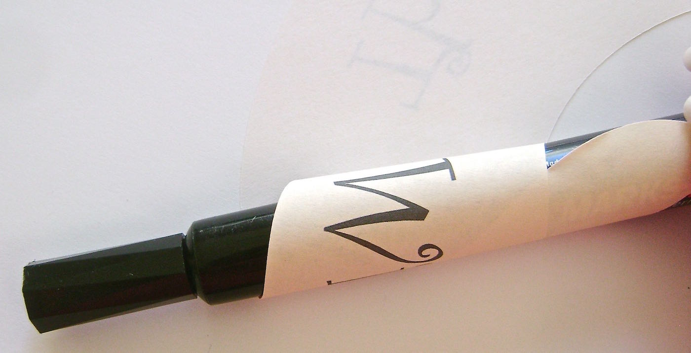 """step 2 - Roll the bottom (the narrow end) of each layer around a large magic marker to create a slight curl in the paper. Only roll as far as the beginning of the word """"With""""."""