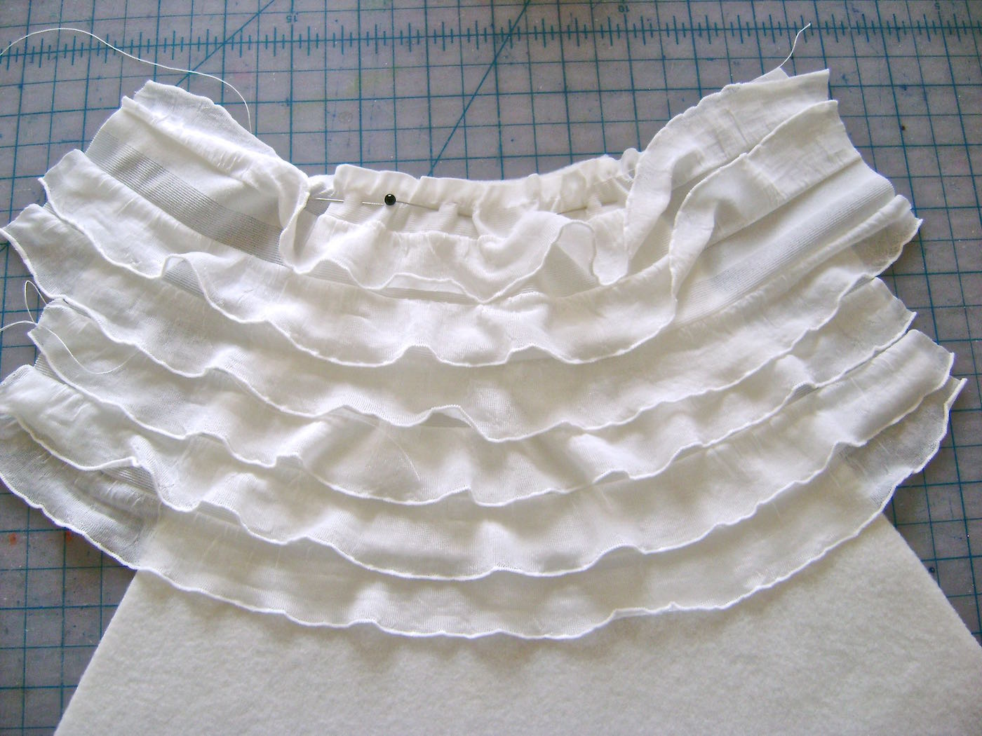 """step 5 - Sew the next 13"""" strip onto the fleece with the bottom edge of the previous ruffle completely overlapping the margin of the new strip. The tails on each side should measure 2.25""""."""