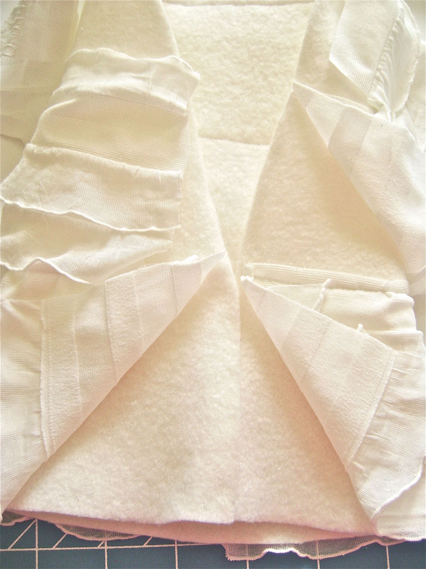 """step 8 - Connect the lower back seam by moving the ruffles aside and overlapping the bottom 3"""" of fleece. Hot glue together."""