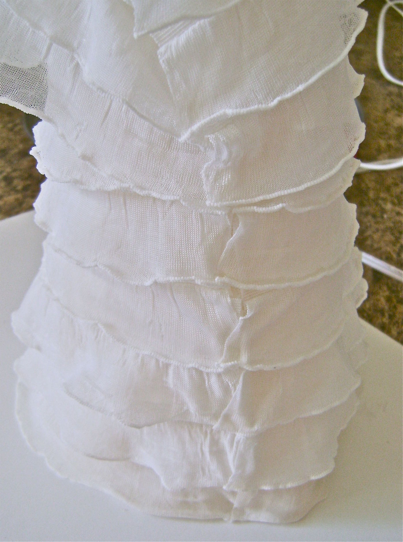 step 18 - When the seam is secure, overlap the ruffle edges and dot with glue to hold them together.