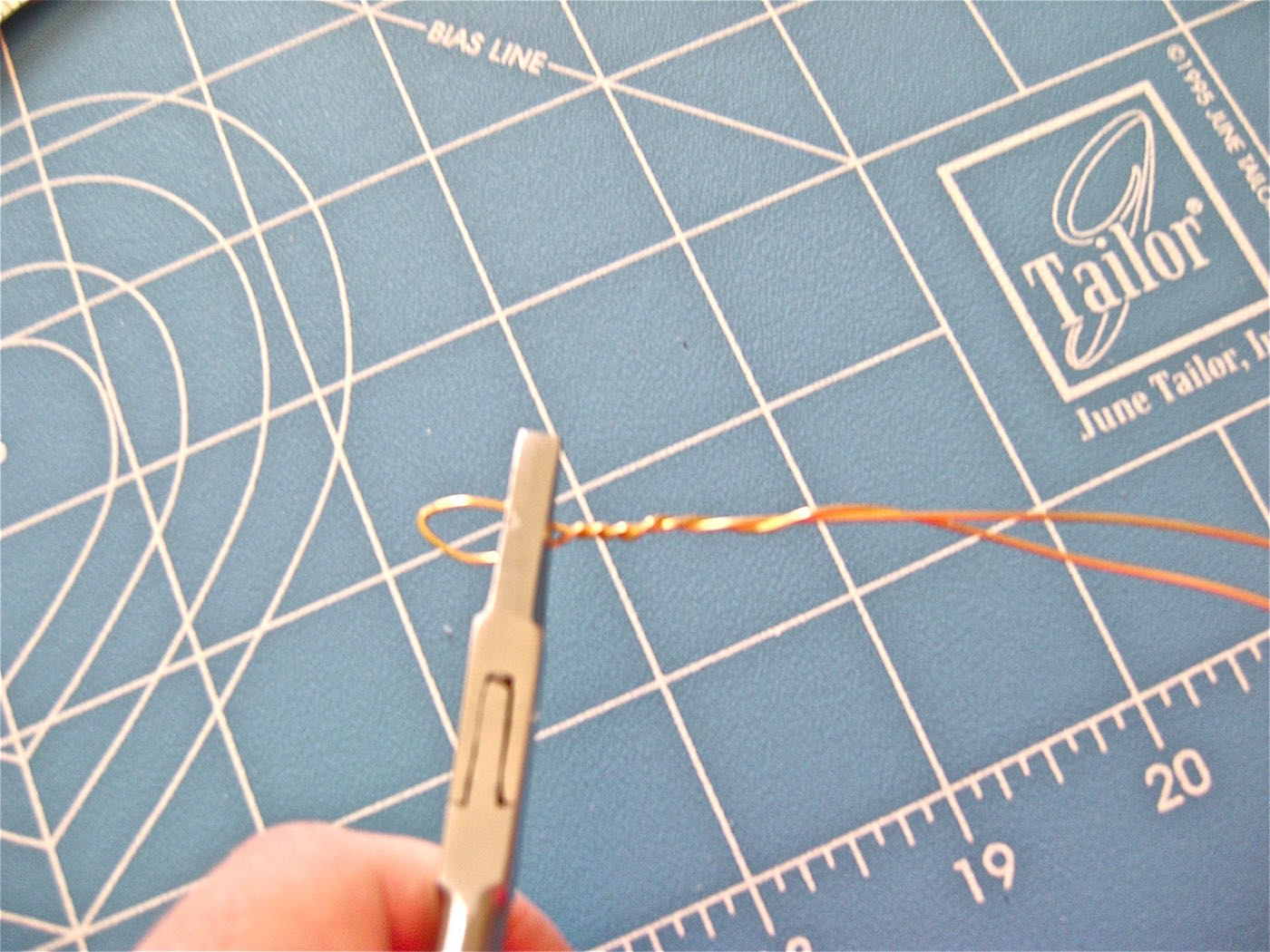 """step 20 -  The Arms   For each arm, cut a 10"""" piece of gold wire. Fold it in half. Holding half an inch from the fold with flat pliers, twist the length of wire to join the two pieces."""