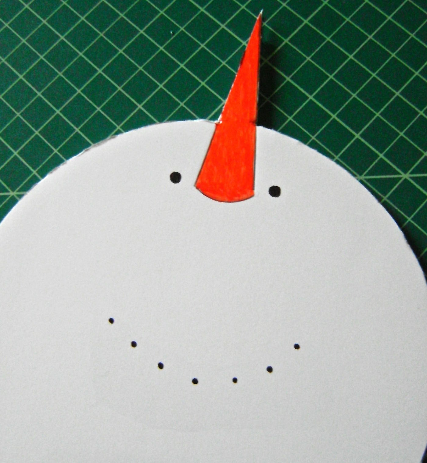step 3 - Cut out the completed snowman shape with the craft knife. Smooth the edges of the foam board with sandpaper. Use orange paint to color the nose. Outline the color with a black marker. Use the marker to create the eyes, mouth, and buttons down the center of the middle circle.