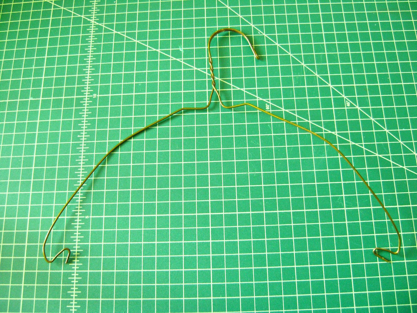 step 6 -  The Mesh Hanger   Twist the white tube between the wire sides of the hanger to remove it. Use pliers to straighten the bent ends and bend both wires over your thigh into an outward arched shape.