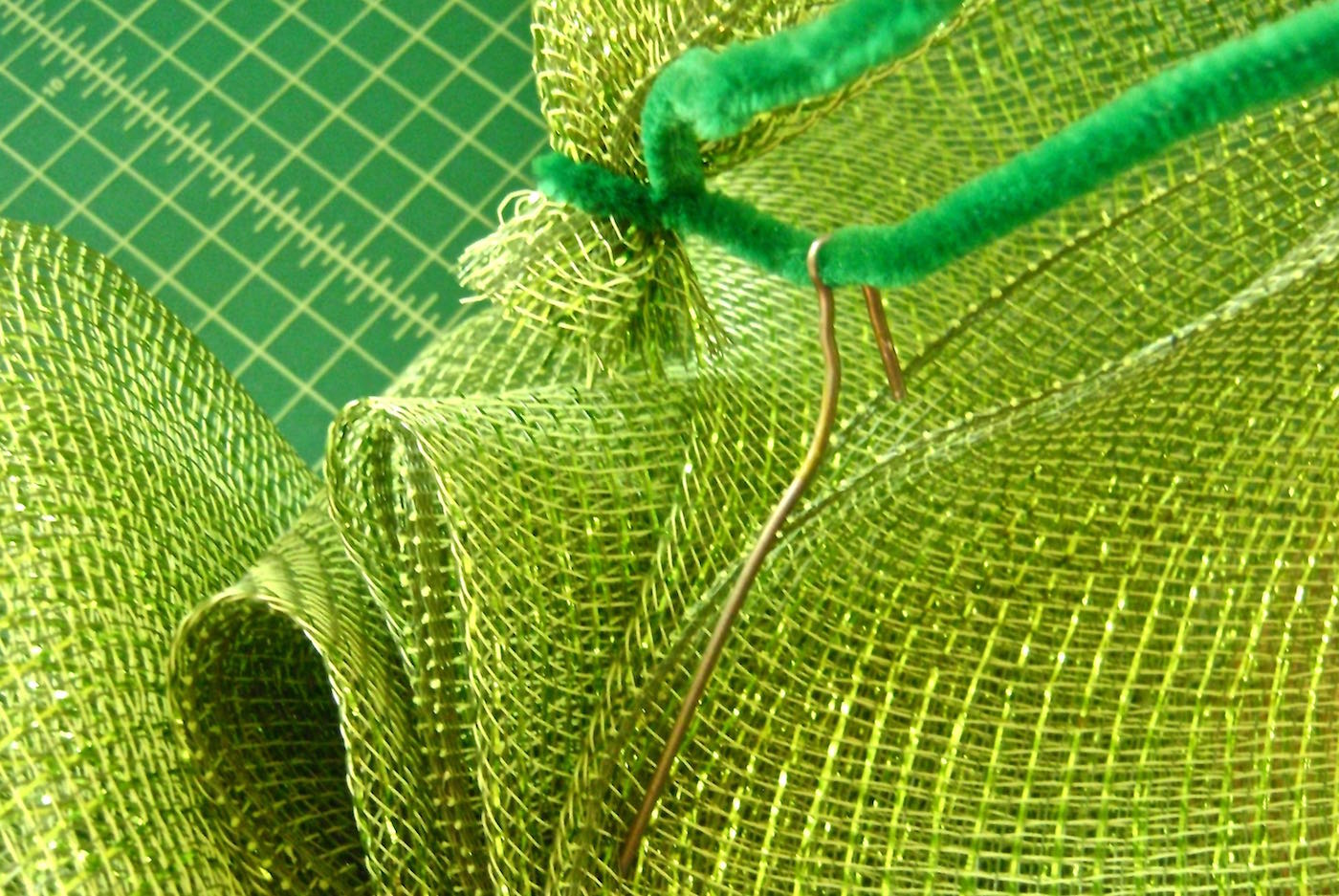 """step 9 - Wrap a pipe cleaner around the mesh end. Attaching the pipe cleaner to the bend in the hanger wire which will form a loop in the 20""""of the deco mesh and conceal the raw edge. Add deco mesh to the other side of the hanger in the same way."""