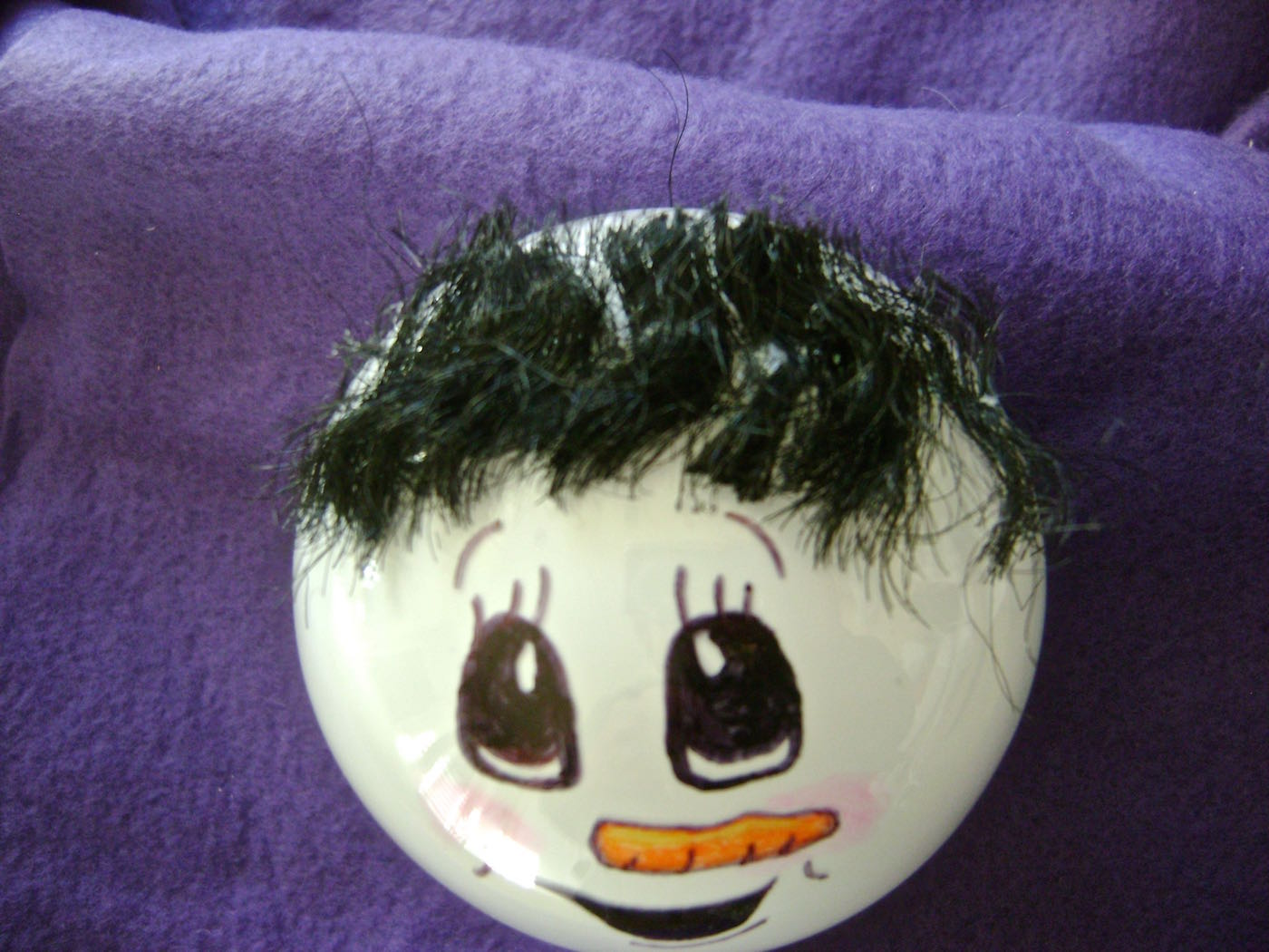 step 6 - Apply hot glue in a line across the top of the head then drape doll hair across the glue line. Don't worry about the hair length. Trim the hair once it is in place and secured to the glue.