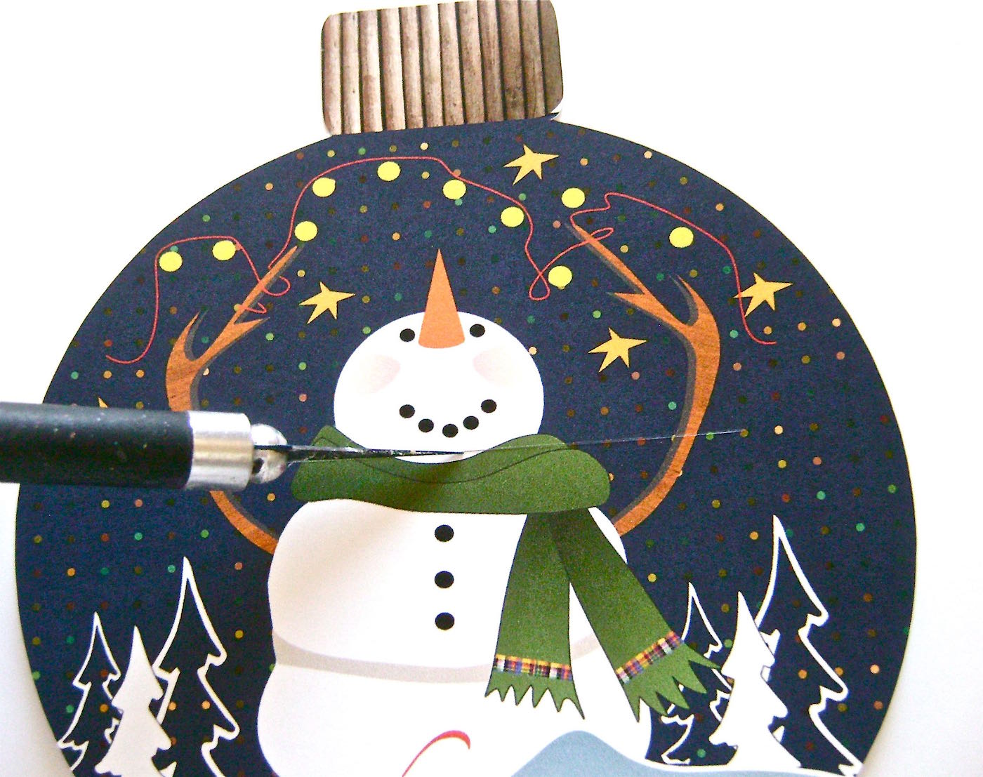 """step 3 - With a craft knife, cut a 2.50"""" wide horizontal slit under the snowman's smile to insert the card. Silhouette users skip this step."""