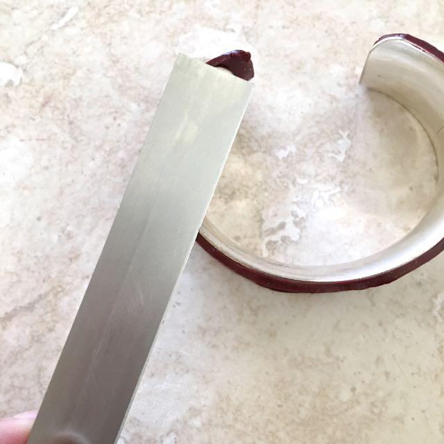 step 16 -Run a tissue blade flat along the metal cuff edges to trim away excess clay.