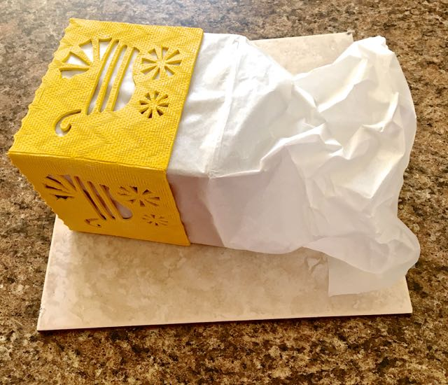 step 18 -Pull out the excess parchment paper from the form. Use it to gently tug the form out of the clay.