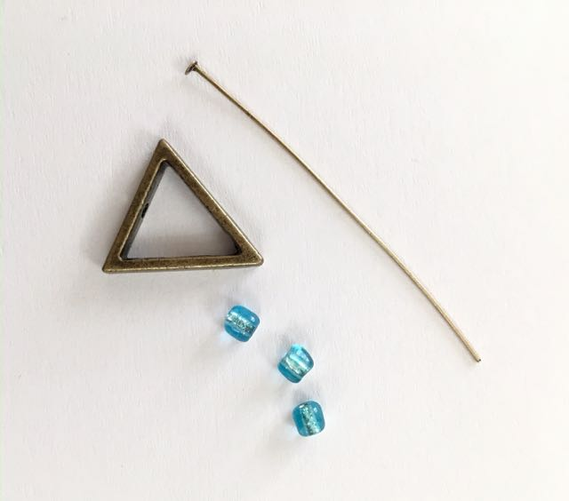 step 1 -  Each triangle element requires a triangle, a nail head wire, and three beads. There are holes in the triangles on the pointy end and the opposite straight edge. Insert the nail head wire into the pointed end of the triangle frame.