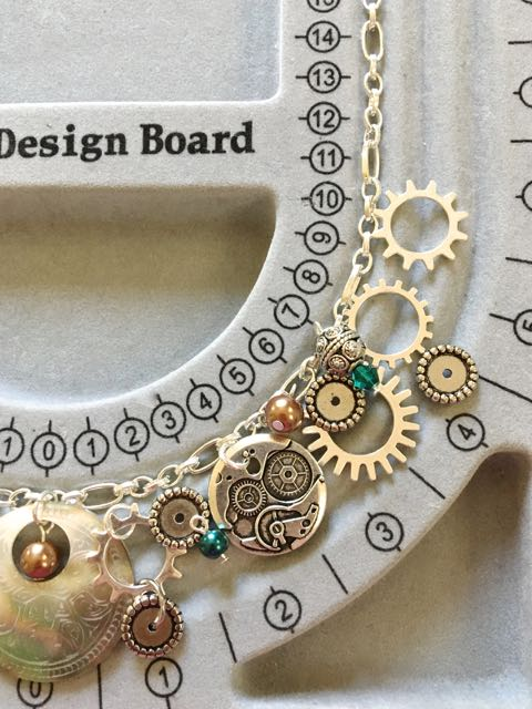 step 3 -Continue experimenting but only on one side of the board. Arrange smaller items like pearls, crystals and other elements with the major pieces.