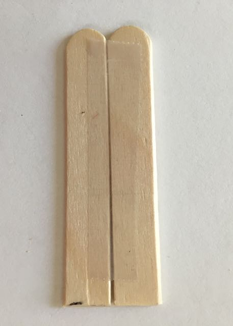 step 4 - Create the slanted roof by hot gluing together two craft sticks. Use tape to hold them together on the back side while the glue is applied if needed. Cut the length of the sticks to fit the roof angle.