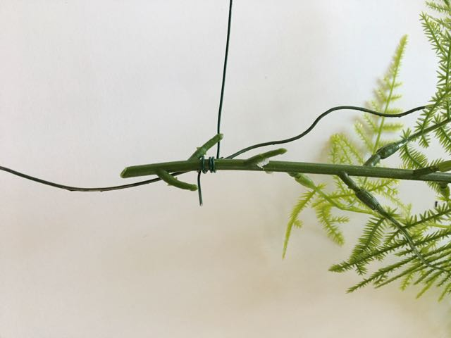 step 23 -Using 24-gauge wire, wrap stems of greenery to the hanger wire, concealing it completely.