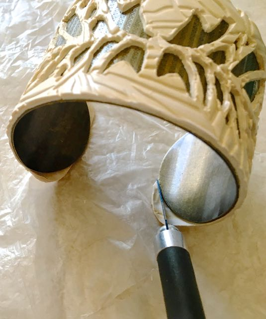 step 13 - Run a tissue blade along the metal cuff edges to trim away excess clay if necessary.