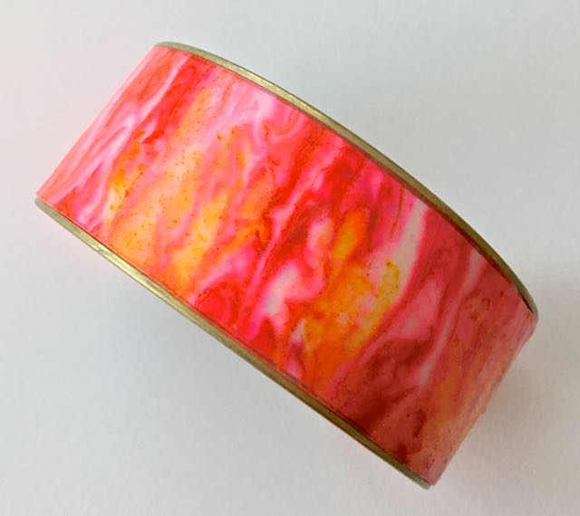 Alcohol ink applied to Clear Transparent LPC is backed with a thin layer of white clay then baked onto the metal bracelet form. The vertical drag technique was used here.