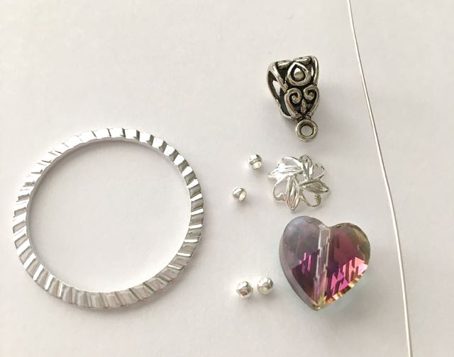 All you need  - C  rystal heart bead, round silver beads, bead cap, wire, bail, and sculpted silver ring