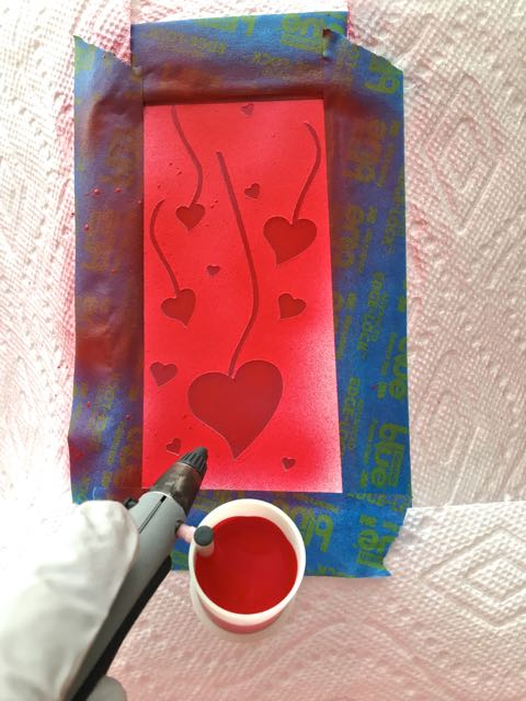 step 3 - Fill a paint cup with red paint. Airbrush the open areas of the stencil. Use several thin applications for coverage. A heavy coat may peel off when the stencil is removed.