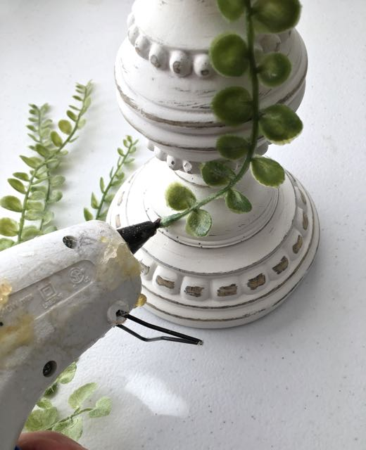 step 13 - Using a glue gun, attach a few greens to the candle pillar.