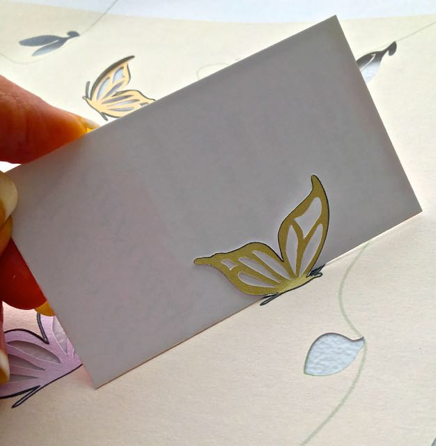 step 7 - Lay the card stock flat. Insert a business card behind each butterfly wing and fold it evenly forward.