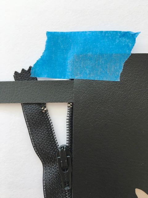 """step 9 - Cut the thin black strip into two 1"""" wide pieces which will act as zipper stops. Place one piece across the top of the zipper, between the two panels, .50"""" from the panel's side edge. Do the same at the bottom of the zipper. Use clips or tape to hold the pieces together."""