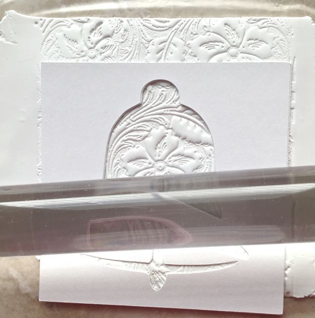 step 5 - Position the stencil on the clay to take advantage of the design elements in the opening. Roll over the lower portion with an acrylic roller, which will slightly flatten the design in the curved line and the space above the clapper.