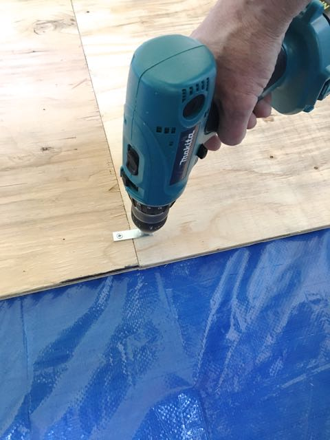 step 3 - With a drill, attach four mending braces to the back of the plywood at equal distances. You will need help to turn the pieces over and apply four braces to the other side.