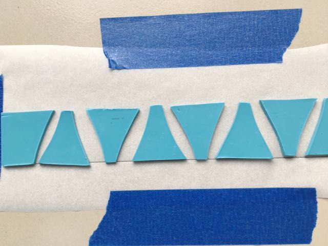 """step 9 - Attach an 8"""" x 2"""" piece of parchment paper to a ceramic tile with painters tape. Draw a straight line horizontally across the paper. Place the turquoise clay pieces on the line with a little spacing between them. This doesn't need to be precise, as you will be adjusting them later."""