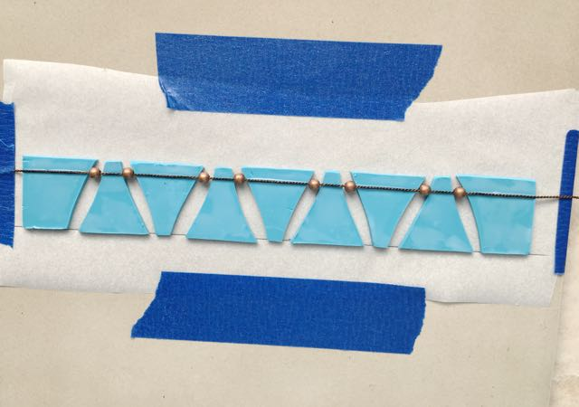 step 15 - Work across the row then tape the cord to the right side of the tile.
