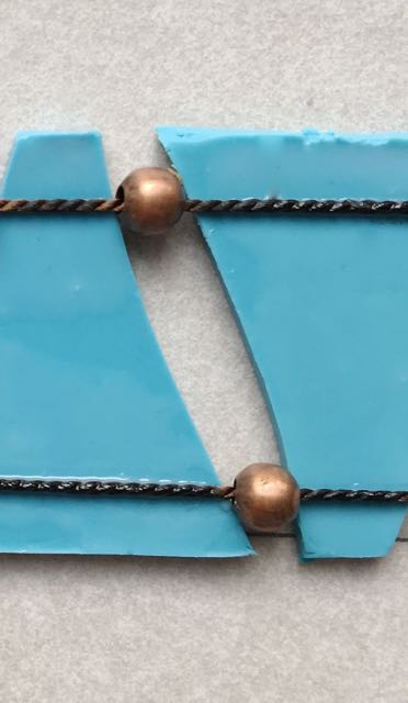 step 17 - Add the second beaded cord to the bottom of the turquoise pieces in the same way. Now is the time to align the clay with equal spacing allowing the beads to rest between pieces.