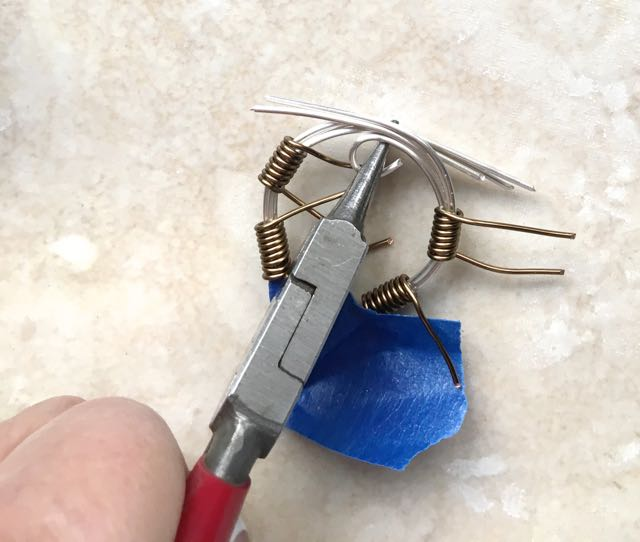 step 10 - Remove the spool. File the sharp wire ends. Use round nose pliers to curl the ends of all six silver wires.