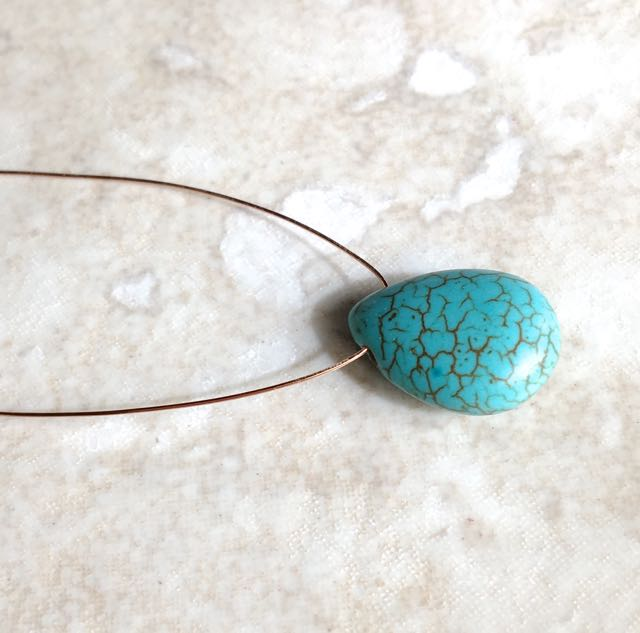 """step 5 - Cut the 26 gauge wire to measure 10"""". Slip the turquoise bead onto the center of the wire."""