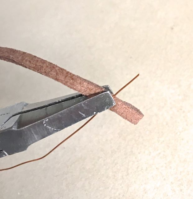 """step 10 - Finish the raw cord ends by folding them over .50"""" to form a loop. Hold the fold together with needle nose pliers. Insert a small length of 26 gauge wire under the pliers so that the end is held securely with the cord."""