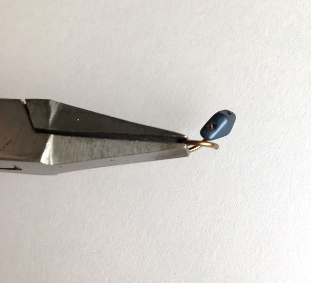 step 3 - Use pliers to open the ring a bit more, enough to insert into a hole in the duo bead. Push the wire into the bead hole until you see the tip of it. (Because the wire is curved, the bead will not slide completely onto the wire.) Using pliers, close the ring so the two cut ends meet.