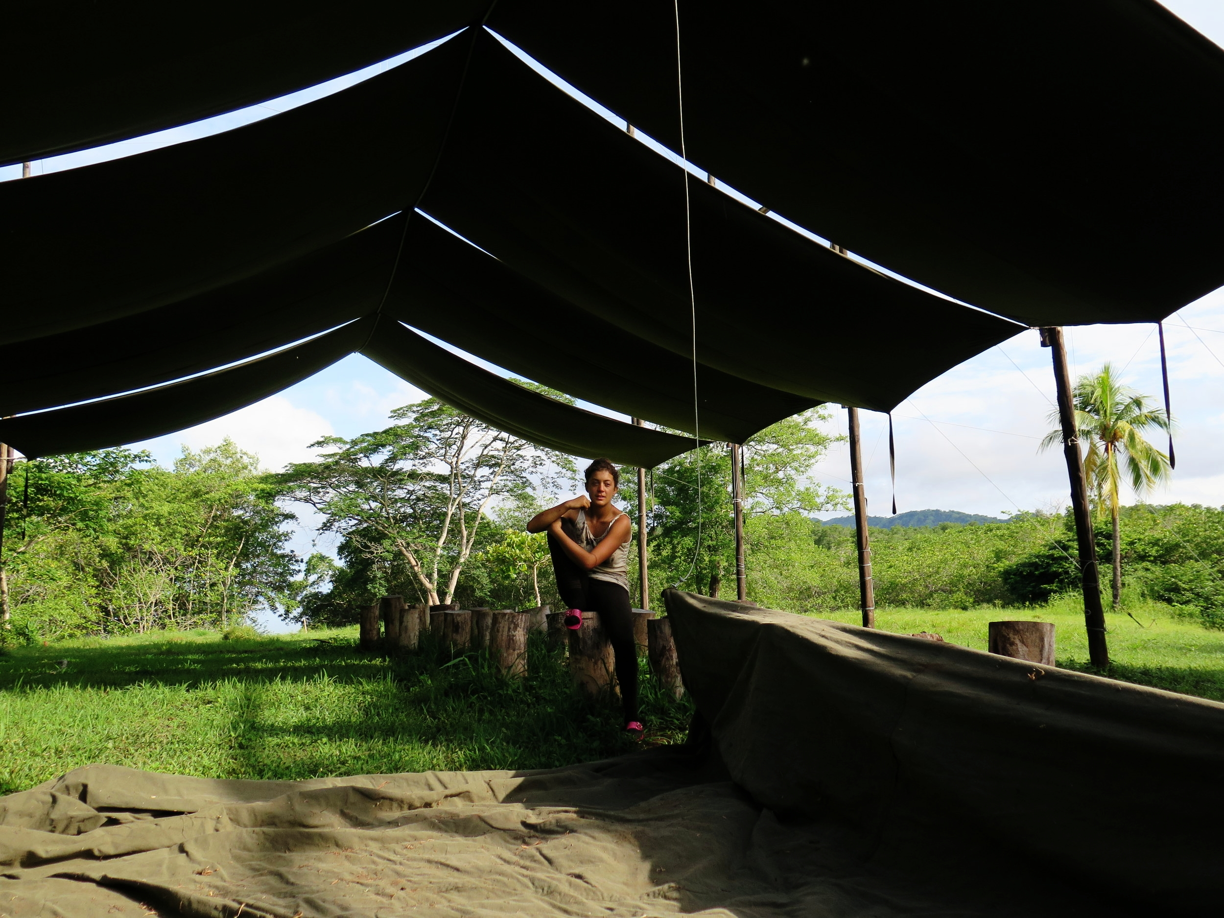 A portrait of Eleanora sitting atop a foundational post, which will soon support the weight of the keel of  Ceiba . She is shaded by the canvas roof. Costa Rican seamstresses built each section of the canvas roof here at the shipyard using our 1958 Singer Sewing Machine, donated and driven down by the Payne family of Arizona.