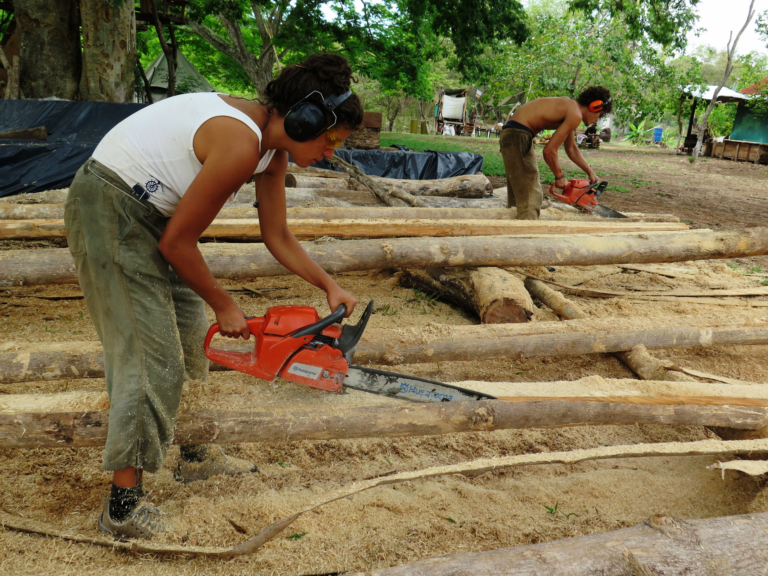 Eleanora and Mate square up round teak posts with the chainsaw.