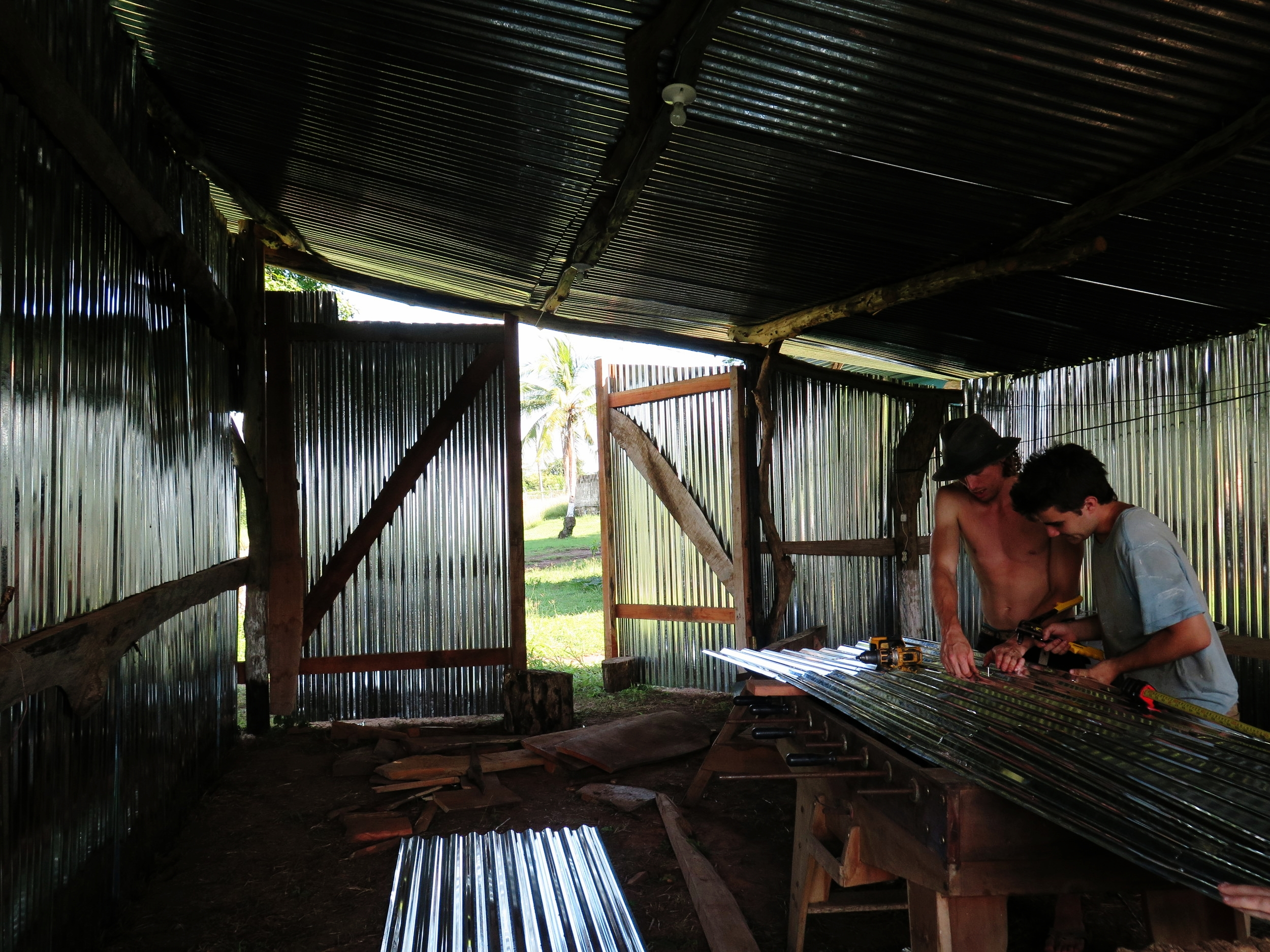 Artur & Chris measuring tin to create walls for the metal workshop.