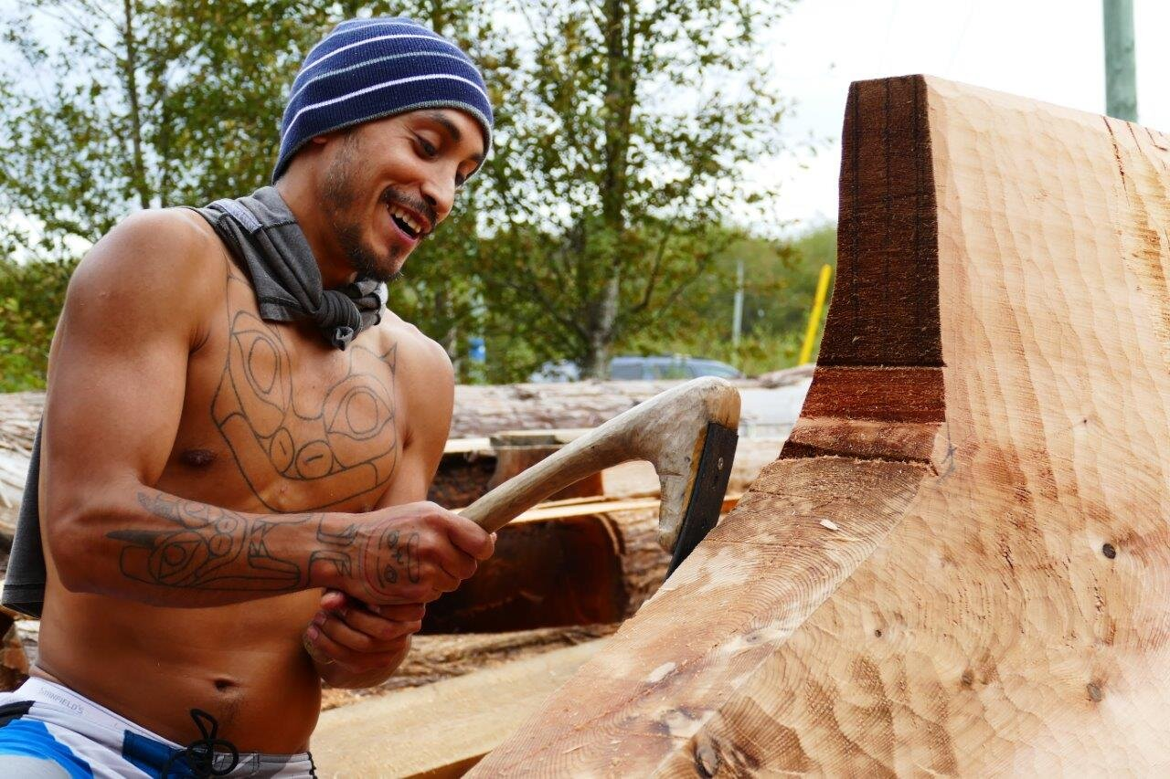 Tyler York works on the canoe, using a leaf-spring adze and crooked alder wood handle.