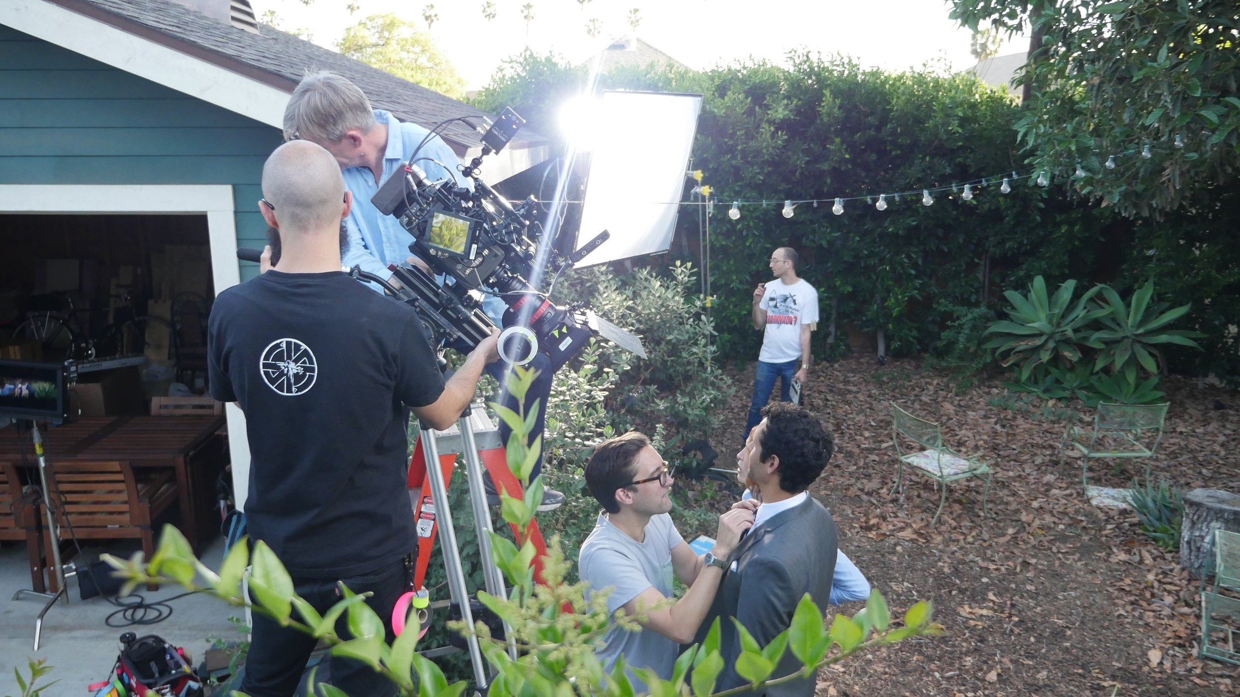 Gareth adjusts Avi's tie while Philip and the crew get ready to roll camera.
