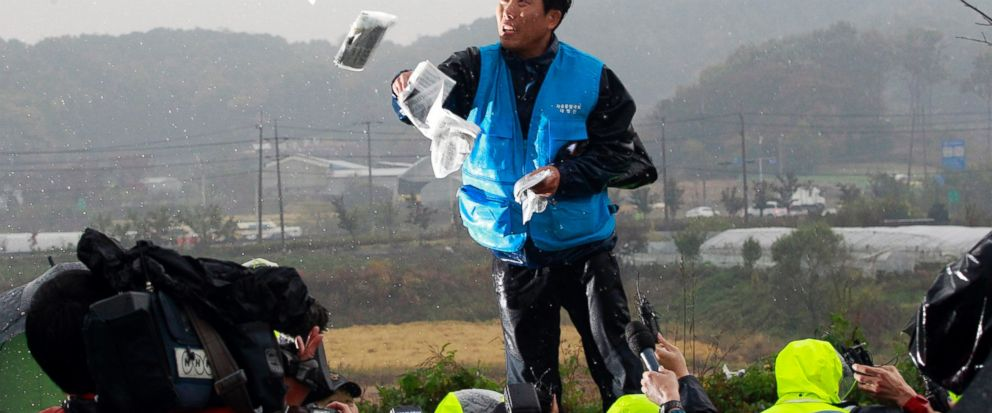 FILE - In this Oct. 22, 2012 file photo, Park Sang Hak, a refugee from the North Korea who now runs the group Fighters for a Free North Korea from a small Seoul office, hurls anti-North Korea leaflets as police block his planned rally on a road in Paju near demilitarized zone, South Korea. In South Korea, political activists send thousands of leaflets, DVDs and flash drives every year across the border into North Korea, mostly by balloon, hoping to bring to the isolated country. (AP Photo/Ahn Young-joon, File)