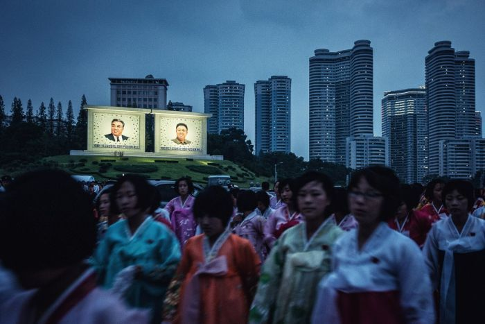 PHOTO:North Korean women gather in front of billboards of Kim Il-Sung and Kim Jong-Il.(Facebook: Michal Huniewicz)