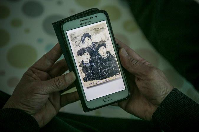 Kim Seok-cheol with a photograph from 1981 in which he is flanked by two friends in Sariwon, North Korea. Credit Jean Chung for The New York Times