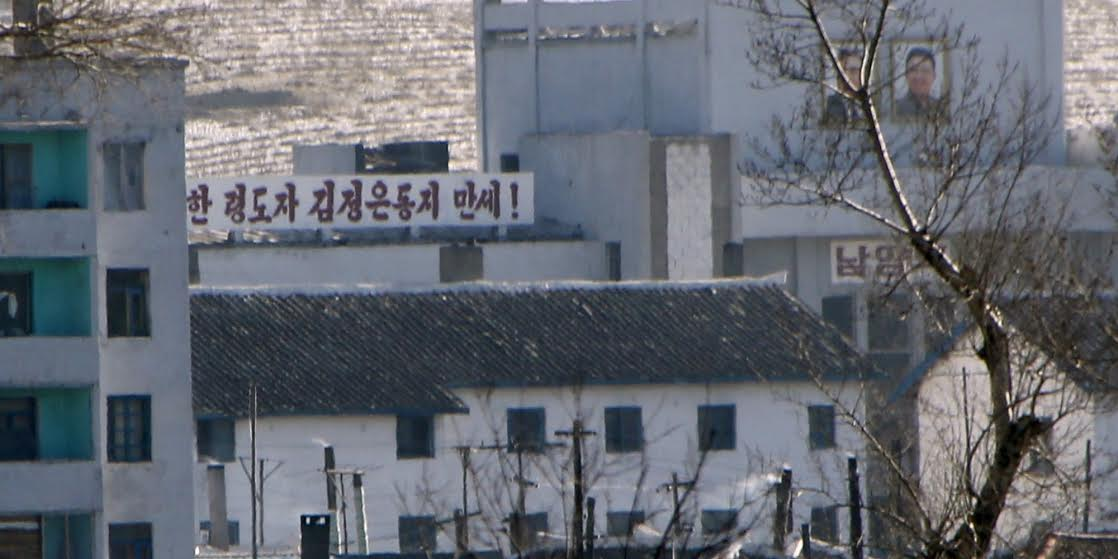 A propaganda slogan and portraits of former North Korean leader Kim Jong Il (R) and his father and founder of North Korea Kim Il Sung (L) are seen in a North Korean village on the banks of the Tumen river, which is seen from the Chinese side in Tumen, China, January 7, 2016.REUTERS/Kim Kyung-Hoon