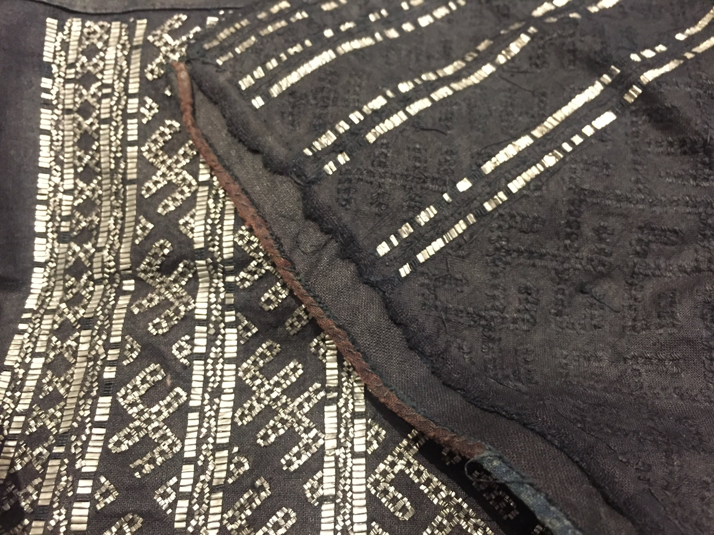 Incedibly, the beautiful black anchoring stiches from the earlier picture will then be made almost invisible by dyeing the fabric in indigo. Slivers of tin strips are then cut and woven by hand into these anchoring stitches, so the embroidery is visible only on the right side of the fabric.
