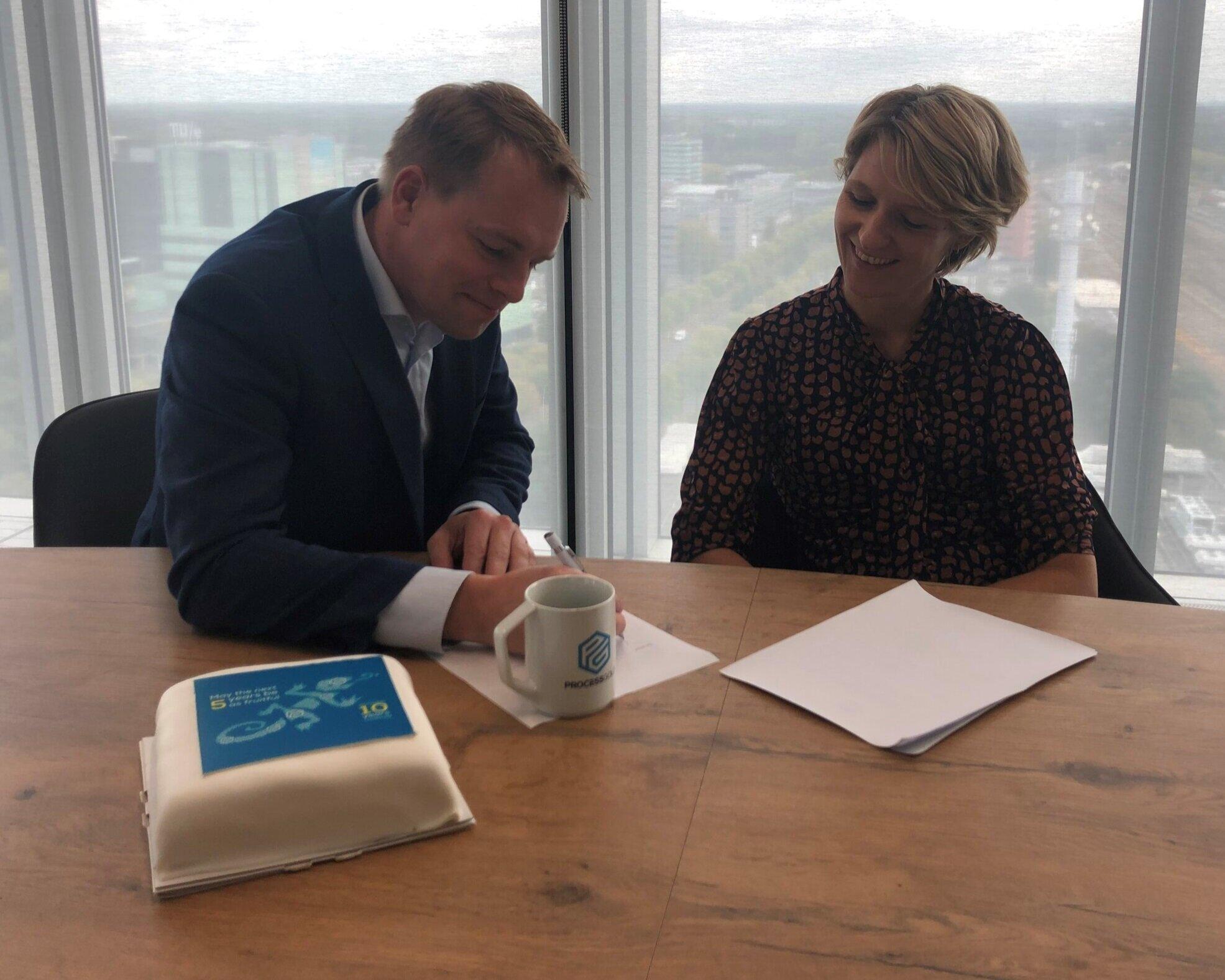 Christiaan Esmeijer van Magnaview en Maaike Goemaat van Topicus tekenen op grote hoogte het contract dat de hernieuwde samenwerking bevestigt. Daarna was er tijd voor taart.